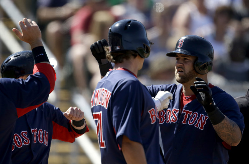 Mike Napoli, right, is welcomed by teammates Thursday after hitting a three-run homer for the Boston Red Sox in a 12-5 victory against the Minnesota Twins.