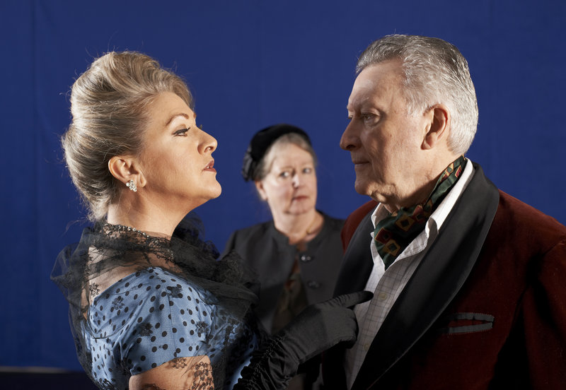 """An old flame, Carlotta Gray (Carol Halstead, left) reunites with Sir Hugo Latymer (Edmond Genest) while his wife Hilde (Maureen Butler) looks on in the Portland Stage Company production of Noel Coward's """"A Song at Twilight."""""""
