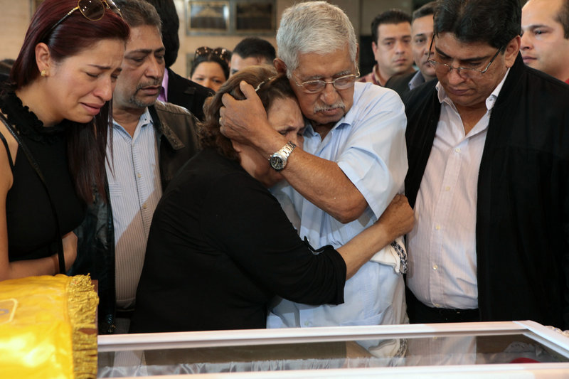 Hugo Chavez's father, Hugo de los Reyes Chavez, center right, comforts his wife, Elena Frias, next to the coffin containing the body of Venezuela's late President Hugo Chavez during his wake Thursday in Caracas, Venezuela.