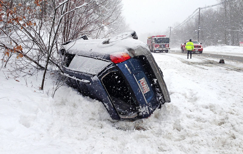 A Subaru Outback is rolled over on Route 20 in Charlton, Mass., near the Sturbridge line, blocking part of the westbound lane Friday.