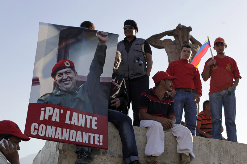 "Supporters of Venezuela's late President Hugo Chavez gather outside a Caracas military academy where leaders from five continents attended a funeral Friday. The poster reads: ""Move forward commander!"""