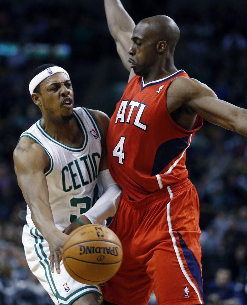 Boston's Paul Pierce slips a pass past Atlanta's Anthony Tolliver during first-quarter action of Friday's game in Boston, won by the Celtics.