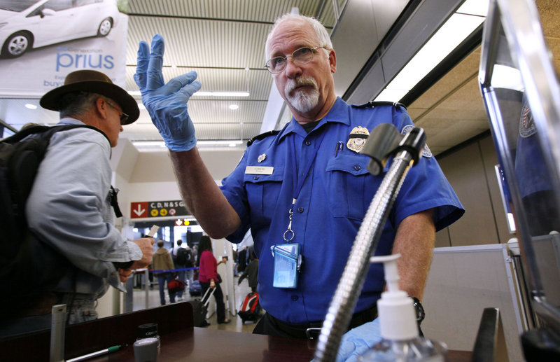 Transportation Security Administration officer Robert Howard signals a traveler forward at a Seattle-Tacoma International Airport security checkpoint in 2010. Airline workers are urging the TSA to rethink a move to allow knives on board airplanes.