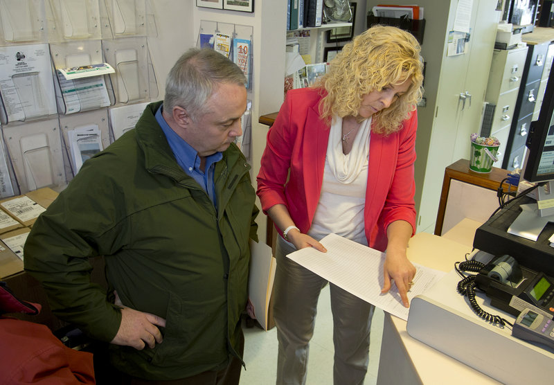 David Francoeur, left, watches as Old Orchard Beach town clerk Kim M. McLaughlin shows Francoeur a blank recall petition at the town office Tuesday, March 12, 2013. Francoeur chairs a recall committee created to recall four Old Orchard Beach town councilors who voted to terminate the town manager's contract.