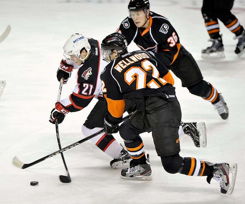 Portland's Andy Miele weaves his way between Adirondack defenders Eric Wellwood, 22, and Erik Gustafsson, 36, during Wednesday's game at the Cumberland County Civic Center.