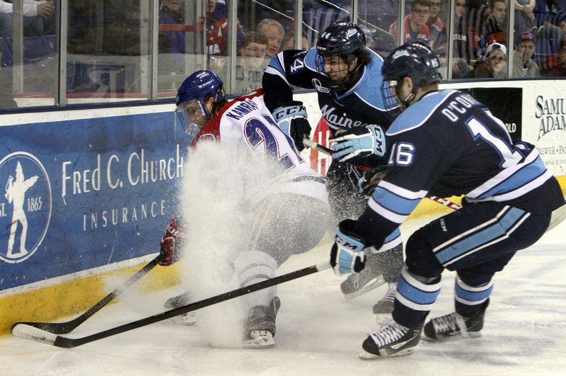 UMass-Lowell's Zack Kamrass tries to avoid being sandwiched by Maine's Brice O'Connor, 16, and Conor Riley, 44, during Thursday night's Hockey East opener at the Tsongas Arena in Lowell, won by the River Hawks 4-3.
