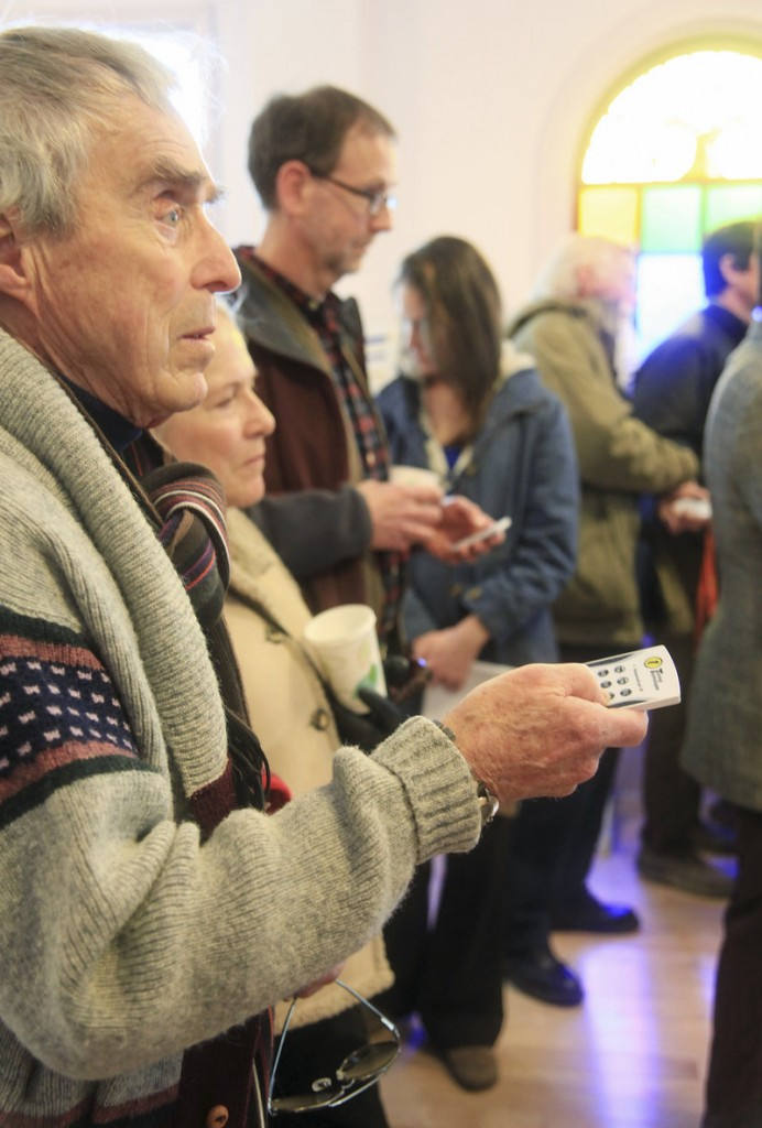 Frank Reilly, left, and his wife, Sharon, of York Street, use hand-held clickers to vote on India Street neighborhood photographs during an informal open house Saturday.