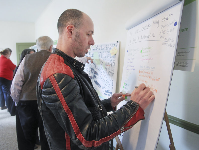 """Markos Miller, a Munjoy Hill resident, shares his opinion on a comment board at Saturday's open house. """"The neighborhood is right between the city and the water. I also like its sense of opportunity,"""" he said."""