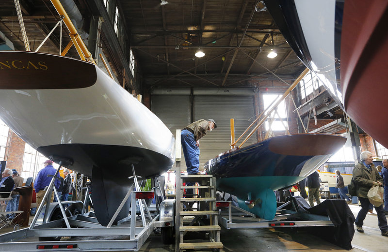A boat enthusiast gets a close-up view of a 25-foot replica of a Herreshoff Buzzards Bay 15, built by Artisan Boatworks in Rockport, during the 26th annual Maine Boatbuilders Show in Portland on Saturday. The show continues Sunday.