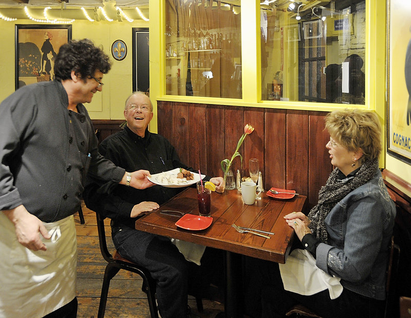 The Merry Table owner and executive chef Jean Claude Vassalle delivers a dessert crepe to Bob and Carolyn Scholl of Connecticut.