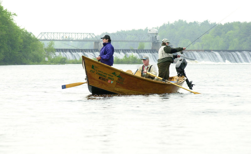 In this 2002 file photo, fishing guide Jim Thibodeau rows a couple of fly fishing clients on the Kennebec River below Shawmut Dam. Maine-based environmental organizations are seeking a federal court order to shut down turbines at four hydroelectric dams on the Androscoggin and Kennebec rivers this spring in order to protect this year's Atlantic salmon run.