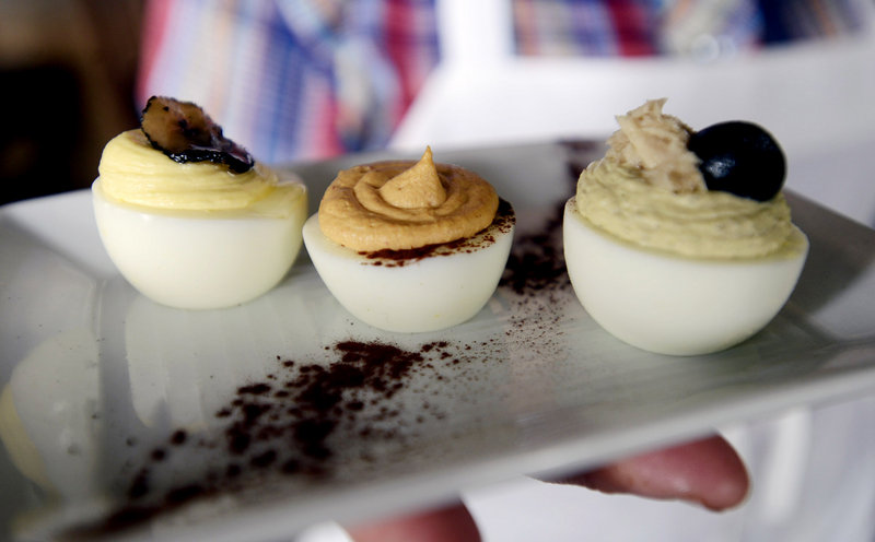 Skye Bonney, sous chef at The Black Birch in Kittery, presents three of her deviled egg specialties: From left, foie gras and truffle, chipotle and cocoa, and nicoise.