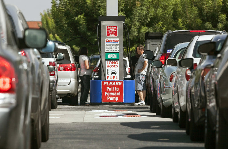 Costco members fill up with discounted gasoline at a Costco gas station in Van Nuys, Calif., in this Oct. 5, 2012, file photo. U.S. oil output rose 14 percent to 6.5 million barrels per day in 2012, a record increase, but you'd never know it from the price at the pump.