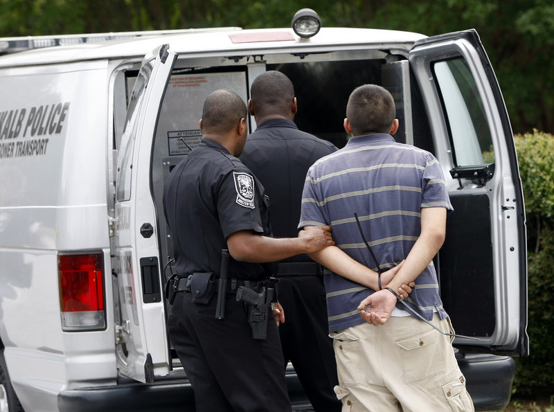 """A suspect is loaded into a DeKalb police prisoner transport van during a """"pill mill"""" raid at Southern Health Management next to police headquarters near Tucker, Ga., in 2012."""