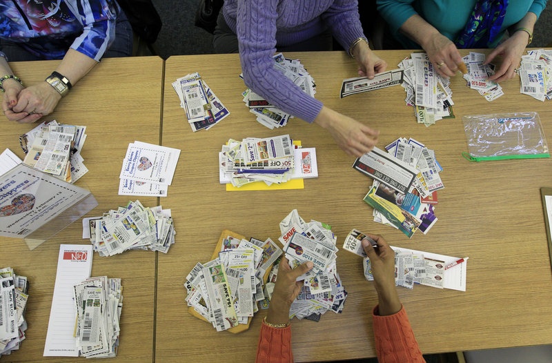 Coupons are sorted as the Savvy Savers Coupon Clippers gather in Garner, N.C., to swap their unwanted coupons for ones they want or need.