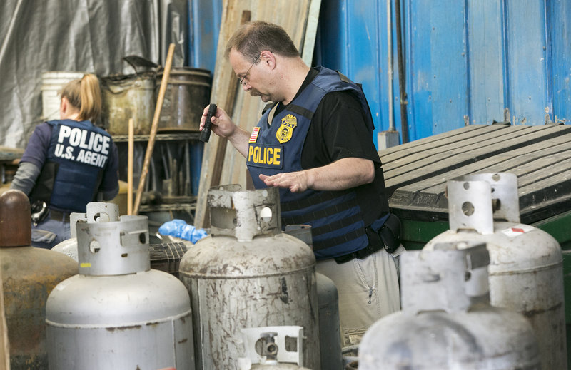 Agents with the Food and Drug Administration's Office of Criminal Investigations search for nitrous oxide tanks in Los Angeles on Friday.