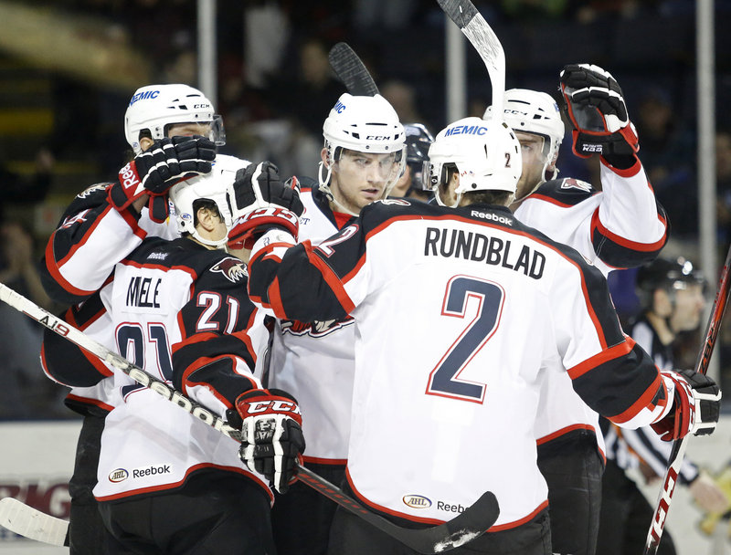 Chris Brown, center, gets the way-to-go from his Portland Pirates teammates Friday night after tipping in a shot in the second period, providing Portland with a 3-1 lead on the way to a 5-2 victory against the St. John's IceCaps.