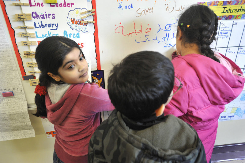 Fatimah Al Shuwaili, 8, and several of her classmates at Saccarappa Elementary School write in Arabic on a classroom white board. Saccarappa has the largest English-language program of Westbrook's three elementary schools.
