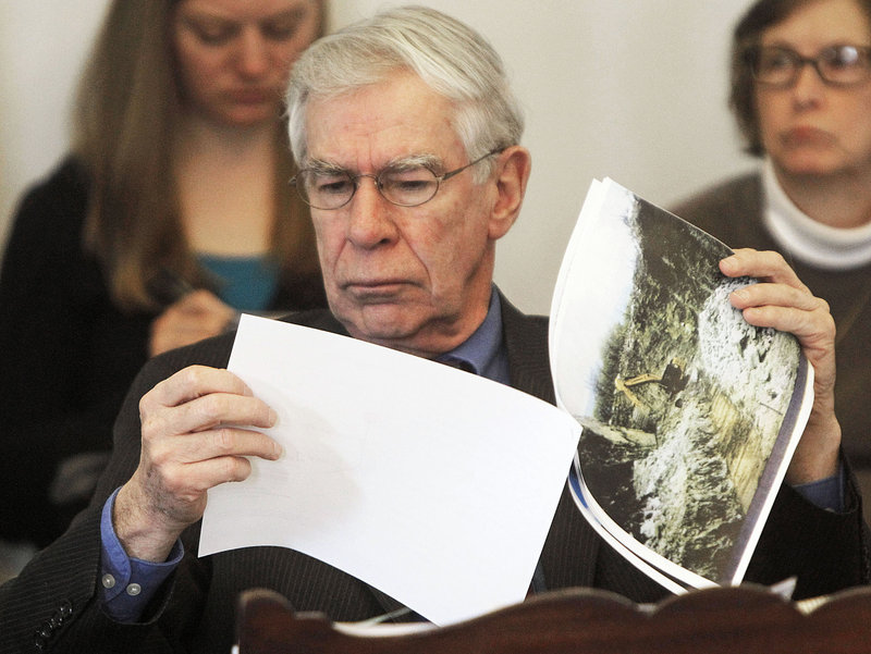 Sen. Donald Collins, D-Franklin, looks at photos of mountaintop wind projects during debate on Tuesday, March 26, 2013 in Montpelier, Vt.