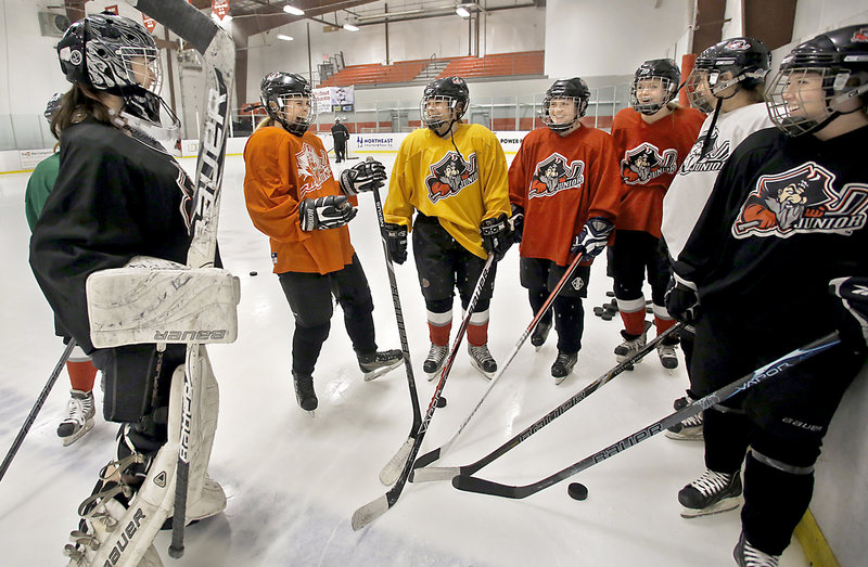 Kendall Carr, on the left, elicits a laugh from her teammates on the Portland Junior Pirates U19 girls' hockey team at a practice in Saco.