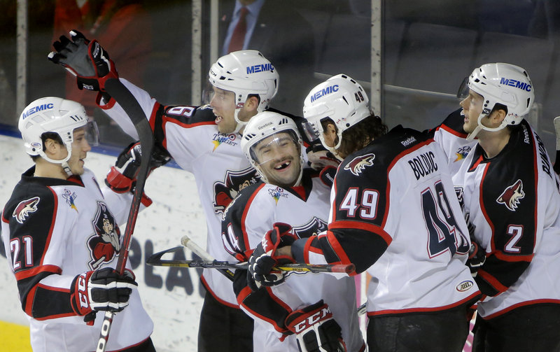 Chris Conner of the Pirates, center, is congratulated by teammates after scoring Friday night in the first period of a 6-3 victory against Manchester.