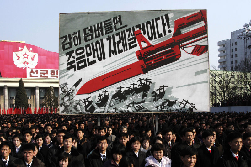 """North Koreans attend a rally earlier this month to support the nation's increasingly belligerent posture toward the West. The sign in the background depicts a large bayonet pointing at U.S. soldiers and says, """"If you dare invade, only death will be waiting for you!"""""""