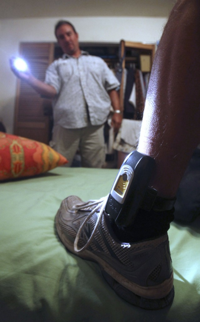Parole agent Steve Nakamura uses a flashlight to inspect a GPS locator worn by a sex-offender parolee in Rio Linda, Calif. California had to replace thousands of the devices recently because they proved easy to thwart.