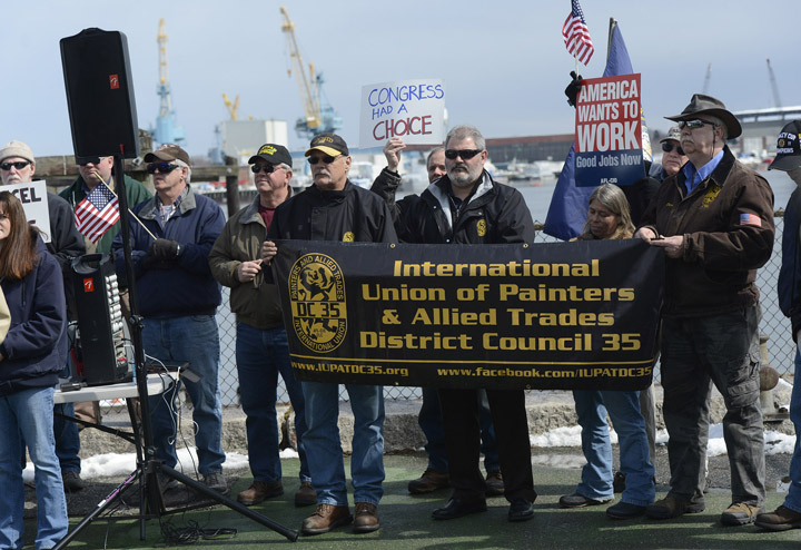 Shipyard workers gather at Prescott Park in Portsmouth, N.H., across the river from the Kittery naval yard, on Thursday to protest the expected shrinking of their paychecks.