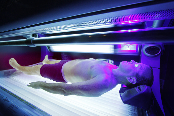 A customer uses a tanning bed at a South Portland tanning salon in this 2010 photo. The American Academy of Pediatrics in 2011 said that anyone younger than 18 should be banned from tanning salons because of the risk of skin cancer.