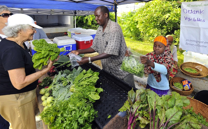 In this 2011 file photo, Nancy Gage of South Portland, left, buys Swiss Chard from Mohamed Abukar, who sells organic vegetables from Fresh Start Farms in Lisbon at the South Portland farmers market. The City Council voted unanimously this week to let the market return to Hinckley Drive in 2013.