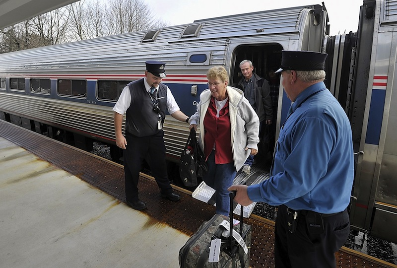 In this Dec. 19, 2012 file photo, Downeaster conductor Chuck Moyer, left, helps passenger, Jean Townsend, who lives in Naples Forida, as she departs the train in Freeport to visit her children for Christmas. Town Manager Peter Joseph proposed a $4.85 million town budget Tuesday, April 23, 2013 that would largely maintain funding for municipal services while accounting for increased costs for the operation of Freeport's train station.