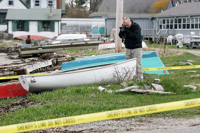 Cumberland County Sheriff's Department Detective Keith Cook photographs a boat near Cook's Lobster House on Bailey Island Thursday as they investigate the discovery of a body along the shore.