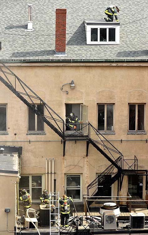 Firefighters check the windows and doors in the back of The Grill Room on Exchange Street Monday.