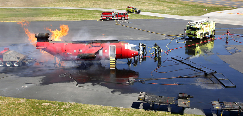 Firefighters practice extinguishing a fire on board a plane as part of an annual FAA training exercise at the Portland International Jetport in Portland on Tuesday.