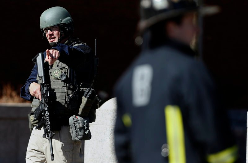 A heavily armed United States Marshall stands guard outside the Moakley Federal Court House in Boston after the building was evacuated, Wednesday, April 17, 2013. (AP Photo/Michael Dwyer)