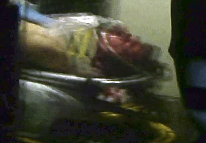 This still frame from video shows Boston Marathon bombing suspect Dzhokhar Tsarnaev visible through an ambulance after he was captured in Watertown, Mass., Friday, April 19, 2013.A 19-year-old college student wanted in the Boston Marathon bombings was taken into custody Friday evening after a manhunt that left the city virtually paralyzed and his older brother and accomplice dead. (AP Photo/Robert Ray) Mass Police Converge