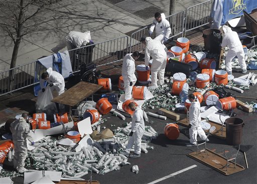 Investigators comb through the post finish line area of the Boston Marathon at Boylston Street on Wednesday, two days after two bombs exploded just before the finish line.