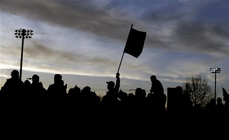 Al Ghoughasian, 50, center, raises a U.S. flag during a vigil for the victims of the Boston Marathon bombing Saturday in Watertown, Mass. Suspected bomber Dzhokhar Tsarnaev is hospitalized in serious condition with unspecified injuries after he was captured in an all day manhunt the day before.