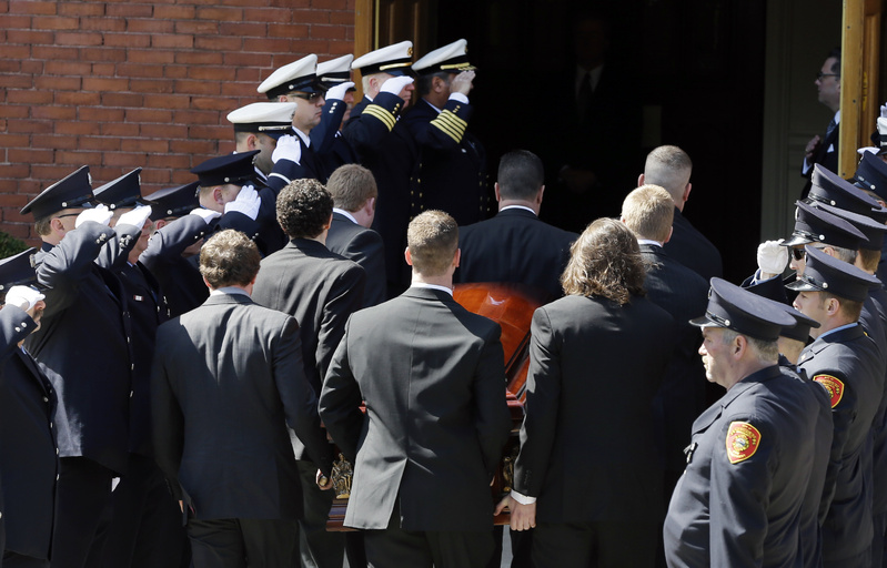 An honor guard from local fire departments salute as pallbearers carry the casket of Boston Marathon bomb victim Krystle Campbell, 29, into St. Joseph's Church for her funeral in Medford, Mass., on Monday.