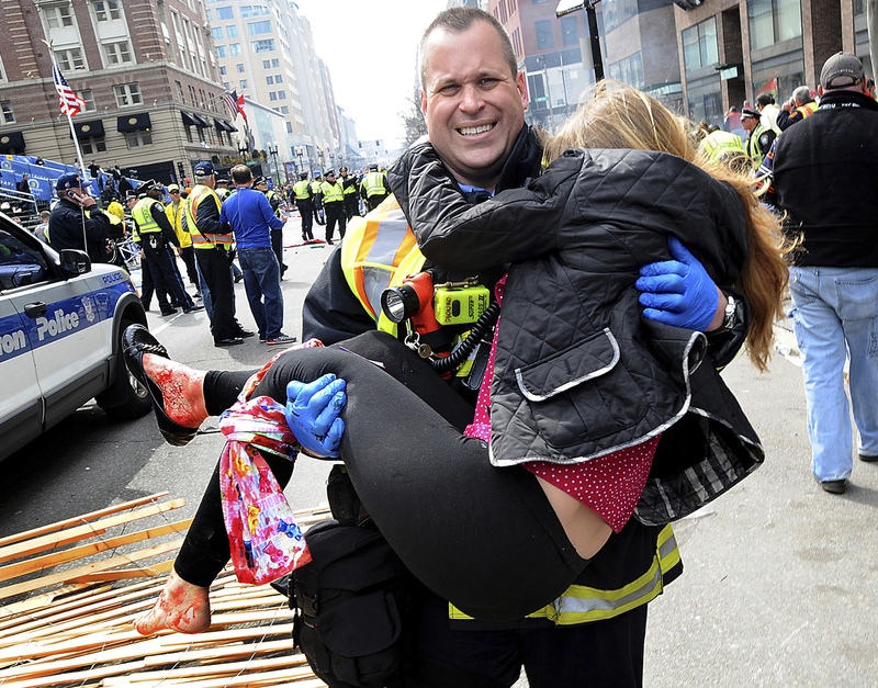 Boston Firefighter James Plourde carries an injured girl away from the scene after a bombing near the finish line of the Boston Marathon on Monday. Doctors say the actions of first-responders saved lives and limbs.