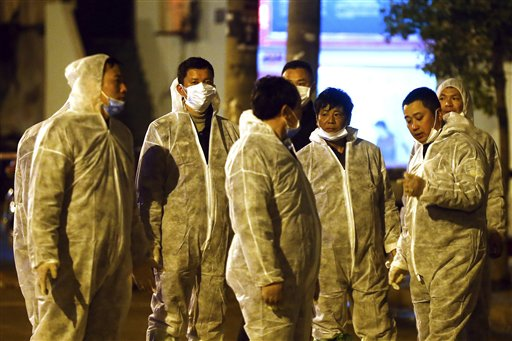 Workers in protective clothing chat during a culling operation as authorities detected the new bird flu strain in pigeons being sold for meat at a wholesale market in Shanghai on Friday.