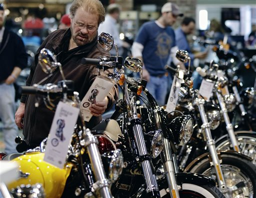 A man examines the price tag on a motorcycle at the Dillon Brothers Harley Davidson dealership in Omaha, Neb. Americans appeared to shrug off a tax increase at the start of the year and spent more in January and February, powered by a stronger job market.