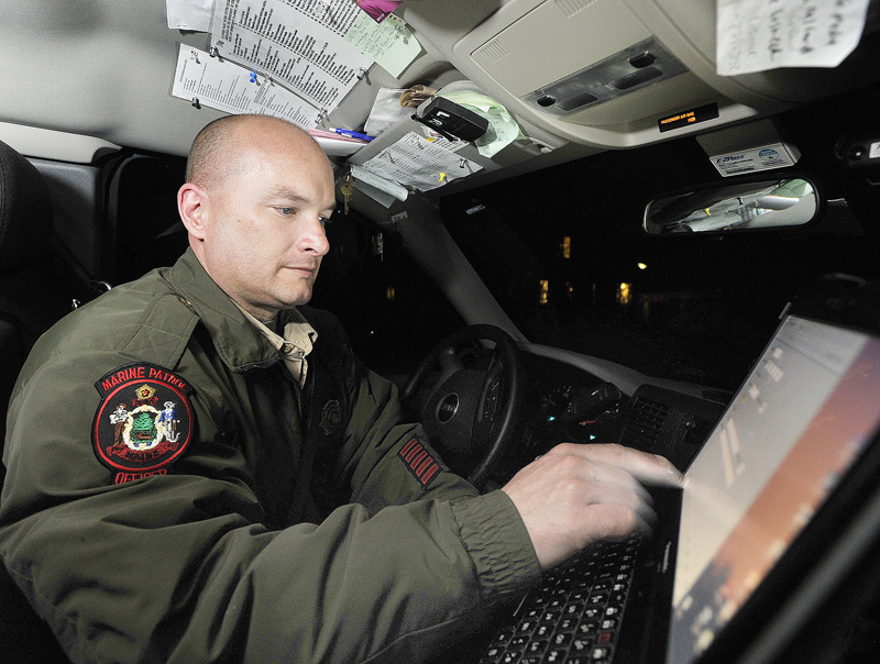 Marine patrol officer Tom Hale uses his computer to check license plate numbers as he keeps tabs on fishermen.