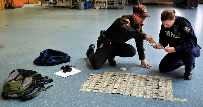 Staff photo by Andy Molloy Somerset County Sheriff's Office Cpl. Gene Cole, left, helps Maine State Police Trooper Diane Vance inventory money recovered from Christopher Knight Tuesday April 9, 2013 at the Pine Tree Camp in Rome. Knight, a hermit who lived in the woods since April 1986, was apprehended when he broke into the camp, police claim. He was captured carrying a knapsack and bag of tools. Many of bills date from the 1980s and 1990s, Vance said, and were never circulated by Knight.