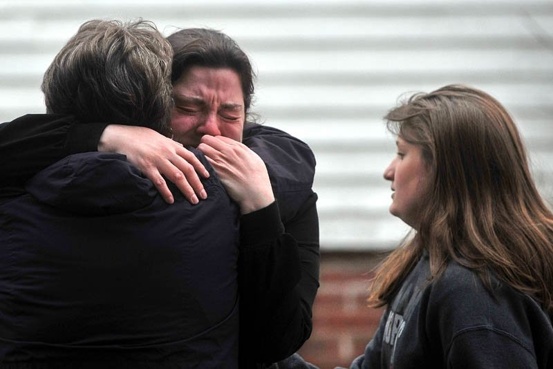 Maribeth Beland, 30, facing, is comforted by an unidentified woman as firefighters from Waterville, Winslow and Fairfield battle a fire at 10 Maple St. in Fairfield, where she lives, on Tuesday.