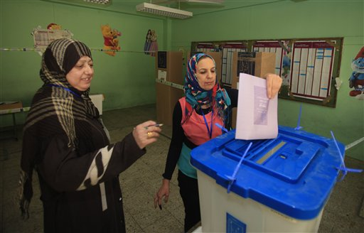 An Iraqi woman casts her ballot at a polling center during the country's provincial elections in Baghdad, Iraq, on Saturday. Polls opened amid tight security for regional elections.