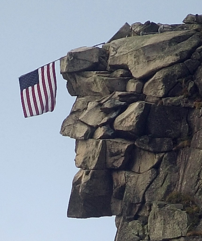 An American flag hangs over the brow of the Old Man of the Mountain in Franconia, N.H., on Oct. 2, 2001.