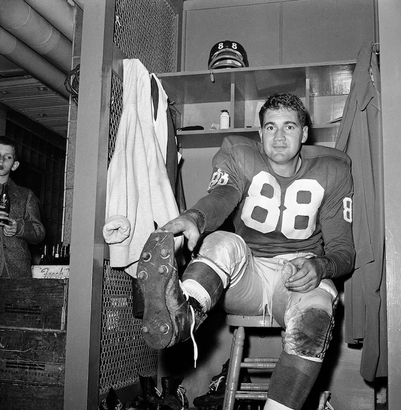 In this Nov. 8, 1959, file photo, New York Giants place kicker Pat Summerall shows off kicking shoe for photographers in the locker room after making three field goals to help the team to a 9-3 win over the Chicago Cardinals at Yankee Stadium in New York. Fox Sports spokesman Dan Bell said Tuesday, April 16, 2013, that Summerall, the NFL player-turned-broadcaster whose deep, resonant voice called games for more than 40 years, has died at the age of 82. (AP Photo/John Lindsay, File)