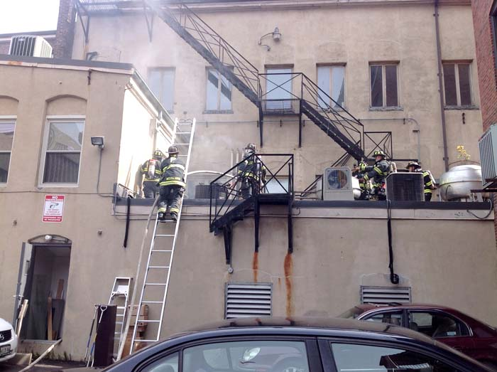 Portland firefighters check the back of 86 Exchange St. on Monday.