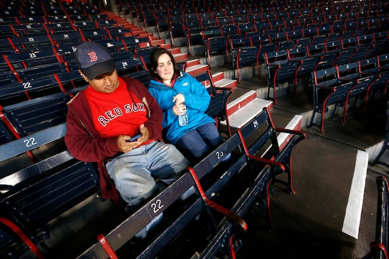 Paul Robinson, left, of Cambridge, Mass., and Madeline Jendzejec, of Somerville, Mass., wait for a baseball game between the Boston Red Sox and the Baltimore Orioles in Boston, Wednesday, April 10, 2013. The Red Sox's nearly 10-year streak of consecutive sold-out home games was expected to end on Wednesday. (AP Photo/Michael Dwyer)